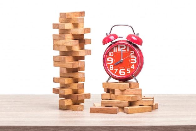 ブロック木製ゲームと木製のテーブルの上の赤い目覚まし時計の山。