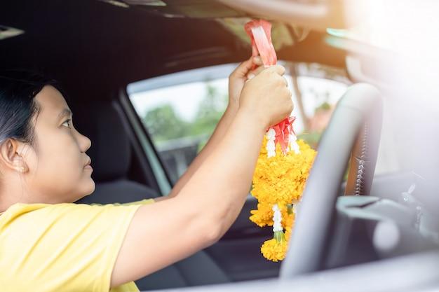 Женщина с цветочной гирляндой в руке и молитва в новой машине для счастливчиков