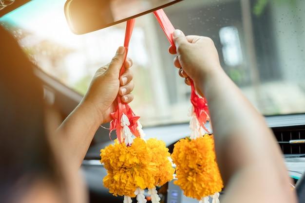 女性の花の花輪を手に、新しい車で幸運を祈る