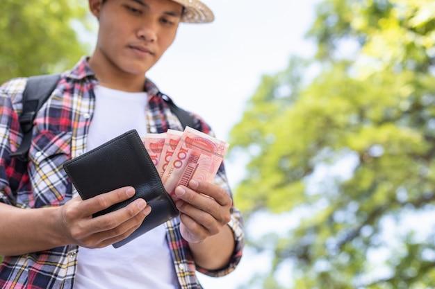 観光名所で彼が見つけた黒い財布に紙幣を数えるか、チェックする観光客