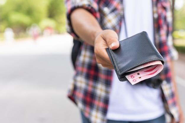 彼が観光名所で見つけた紙幣と黒い財布を与えるアジアの観光客の手。
