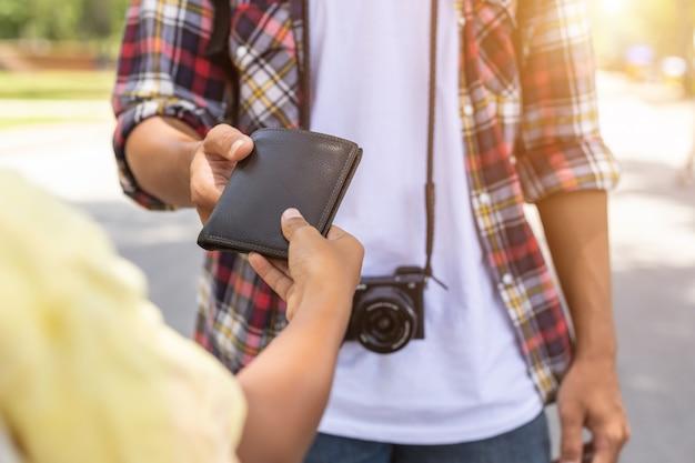 アジアの観光客が観光名所で見つけた他の人から彼の黒い財布を拾う