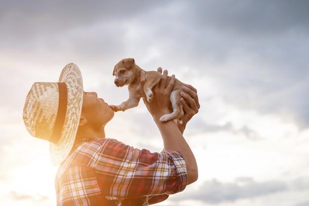 仕事の後の夕方に彼の茶色の小さな子犬と遊ぶ若いアジア農家