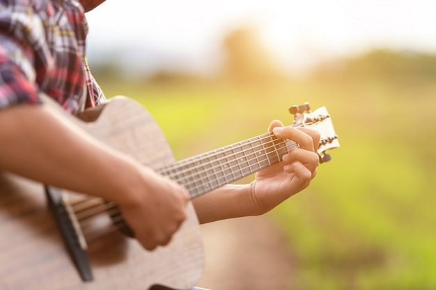 日没時間の緑の田んぼでギターを弾くアジア人
