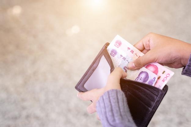 黒い財布に紙幣をチェックする人