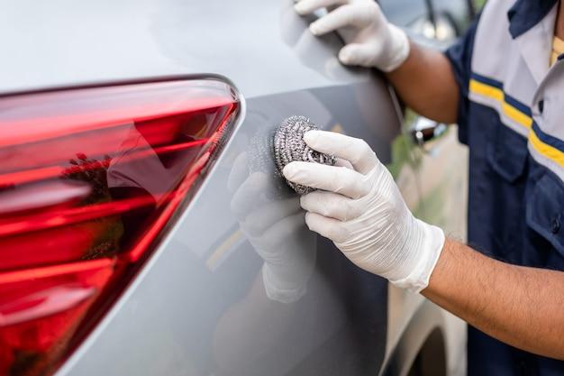 Лицо, использующее шерсть из нержавеющей стали для полировки поверхности автомобиля
