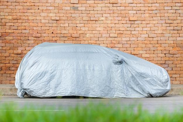 Покрытие автомобиля серебристой тканью парковка на дороге