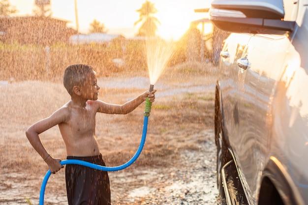 朝の時間で屋外で車を洗うにホースとスプレーから水を再生する幸せなアジア少年