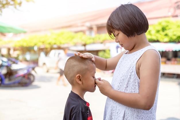 泣いている若いアジアの少年と彼の姉は励まそうとする