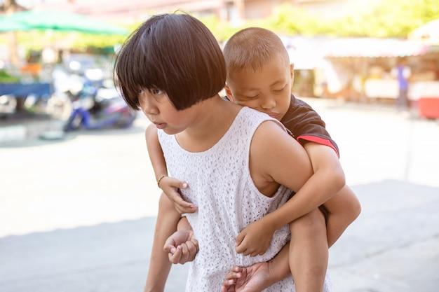 若い男の子は彼の姉に乗って、通りを歩いて