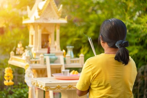 Задняя сторона тайской женщины, стоя перед домом амулета и молиться с ладаном