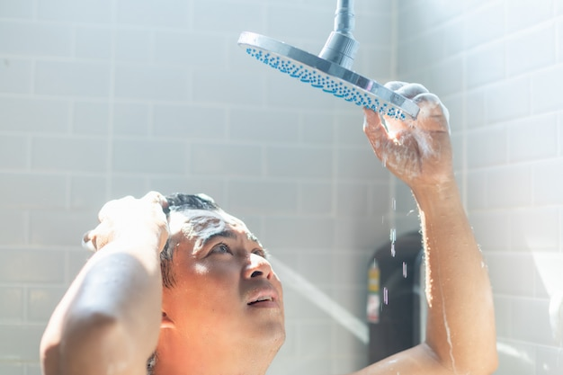 心配しているアジア人はシャワーを浴びます