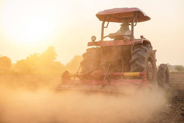 土を準備する土地の大きなトラクターでタイの農民