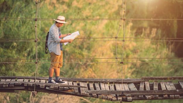 古くて壊れた木製の橋の上を歩いてアジア観光客の男
