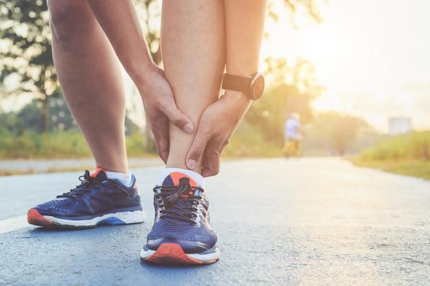 アジア人は公園の道を走っている間彼の足首を保持します