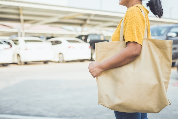 Женщина использует хлопковую сумку в торговом центре, чтобы заменить использование полиэтиленового пакета