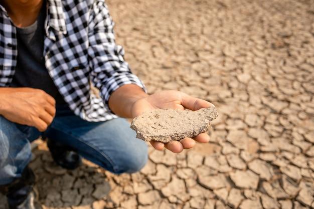 農家は乾燥した川に立ち、スコータイの空の水を探しています。干ばつシーズンのコンセプト