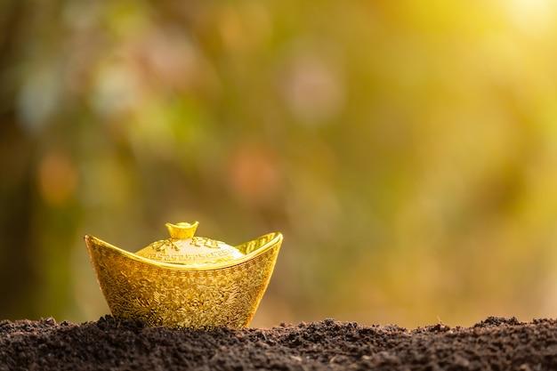 庭の土の山の上に中国の新年装飾の金塊は、背景をぼかし