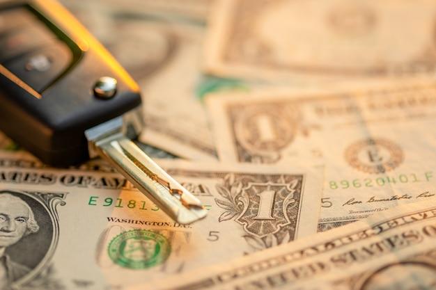 Новые ключи от машины с банкнотой доллара сша на деревянном столе. концепция покупки или аренды автомобиля