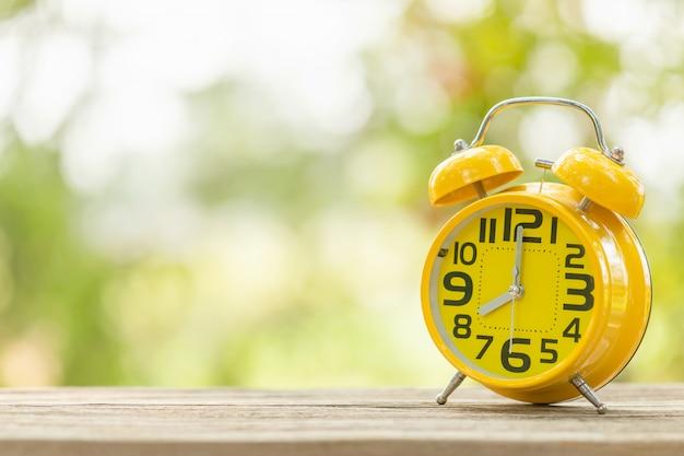 緑の屋外の自然のぼかしと木製のテーブルの上の黄色の目覚まし時計