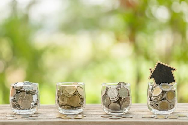 木造住宅モデルと木製のテーブルに明確な瓶にコイン。ホームコンセプトのお金の節約