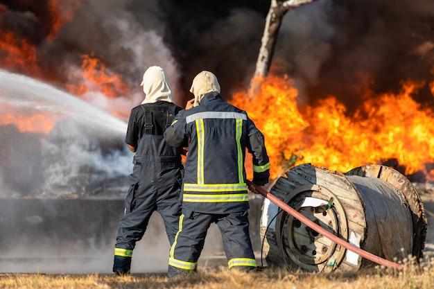 大きな水ホースから水を噴霧して消防士が火災を防止