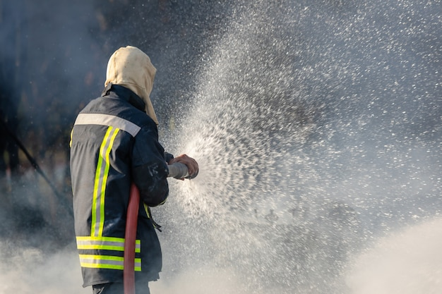 Пожарный распыляет воду из большого водяного шланга, чтобы предотвратить пожар