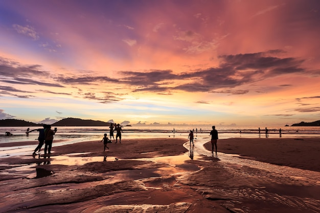 夕日にビーチで遊ぶ人々のシルエット
