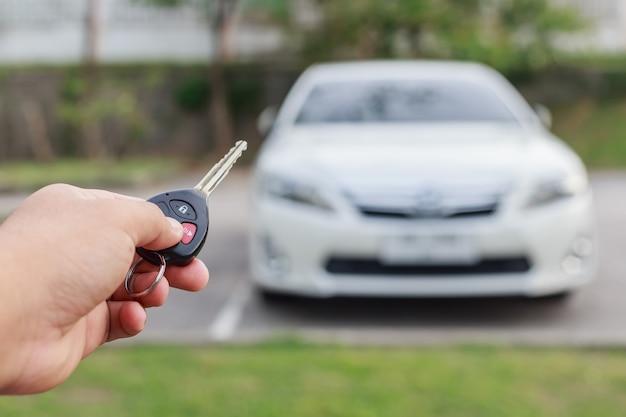 新車のキーを持っている女性の手を閉じます