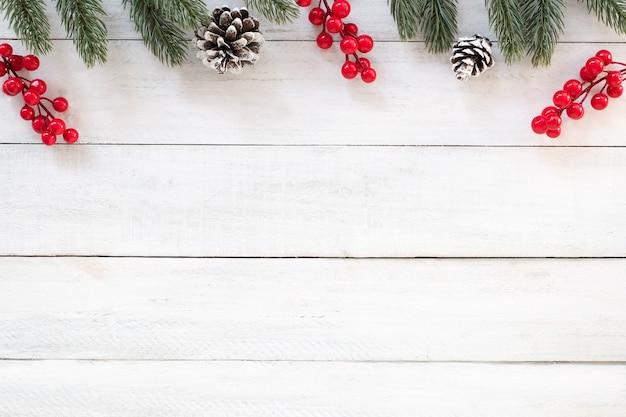 クリスマスと新年の背景には、白い木の背景にモミの枝、ホリーベリーと松のコーン。クリエイティブフラットレイ、コピースペースを持つトップビューデザイン