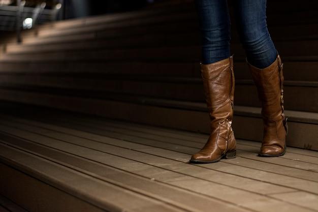 階段を下って歩くレザーブーツの少女