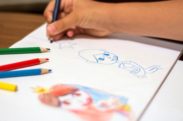 木製の色鉛筆で描く小さな女の子