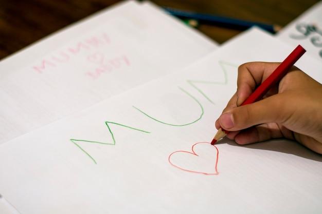 小さな女の子が心臓の形を描く
