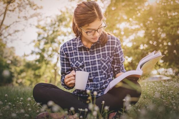 緑の草の上にコーヒーの杯で座っている本の女の子