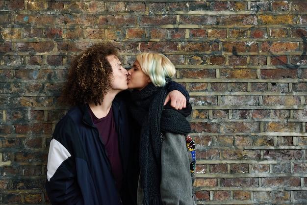 ロンドンの典型的なれんが造りの壁の前でカムデンの町を楽しむ若いカップル