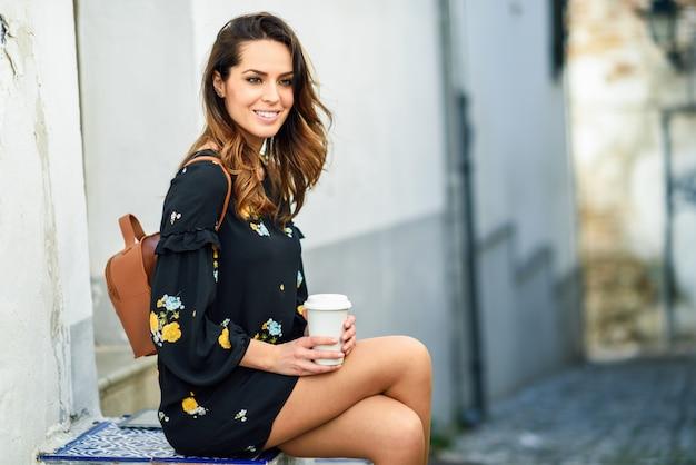 Среднего возраста путешествия женщина сидит, попивая кофе.