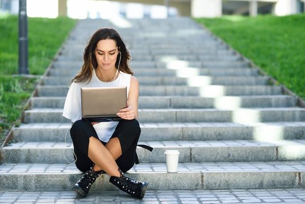 若い女性が床に座って彼女のラップトップコンピューターを操作します。