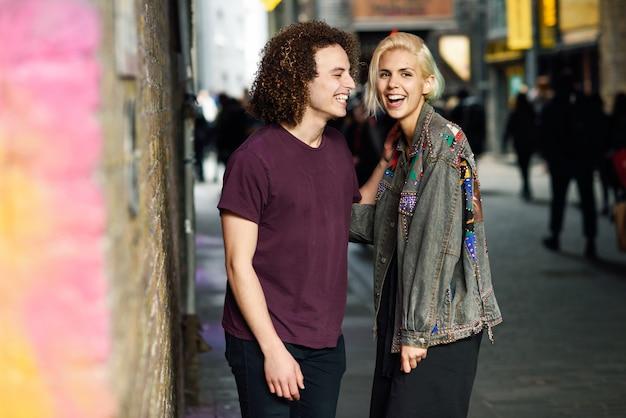典型的なロンドンの通りに都市の背景で話している若いカップル。