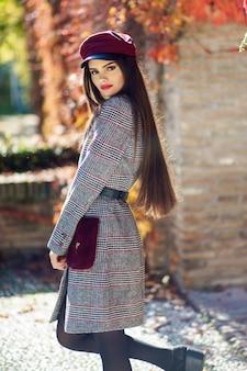 冬のコートと秋の葉のキャップを身に着けている非常に長い髪の美しい少女