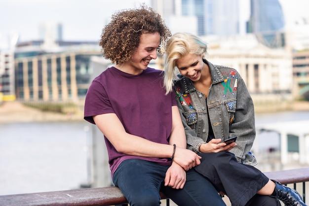 テムズ川のそばに座って話している幸せなカップル。