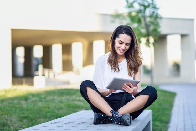 都市の背景に屋外に座ってデジタルタブレットを使用して若い女性。