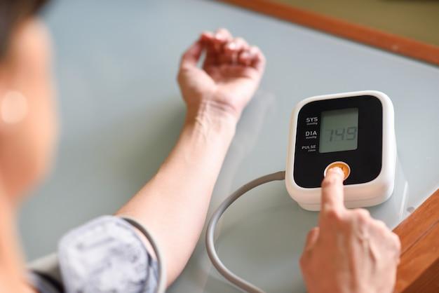 女性が自宅で自分の血圧を測定します。