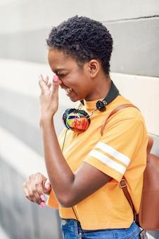 Счастливая чернокожая женщина смеясь над на городской стене с глазами закрыла.
