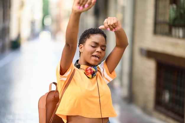 若い黒人女性は夏に路上で踊っています。