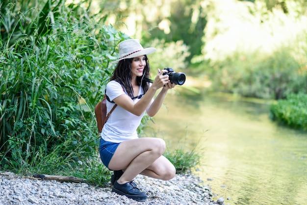 ミラーレスカメラで写真を撮るハイカーの女性