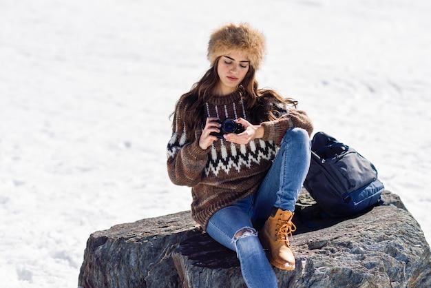 雪の山で写真を撮る若い女性
