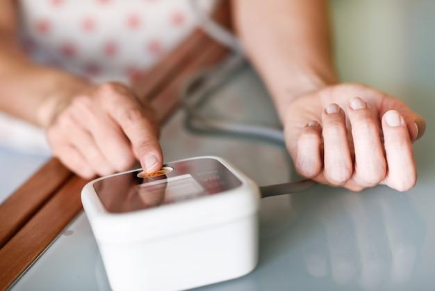 Женщина, измерения ее собственного кровяного давления в домашних условиях.