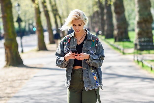 都市公園の通りを歩いてスマートフォンを使用して現代の髪型を持つ若い都市女性。