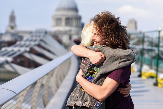 ロンドンのテムズ川、ミレニアムブリッジで抱いて幸せなカップル。