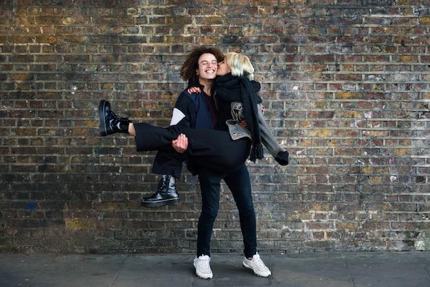 Мужчина держит свою подругу на руках перед кирпичной стеной, типичной для лондона